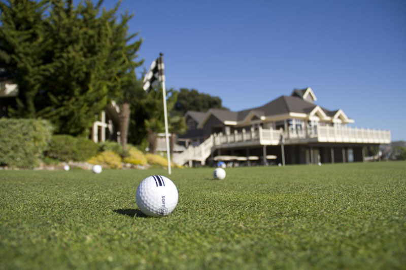 Several golf balls sit on the course in view of the clubhouse at Avila Beach